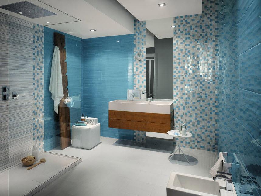 Una excelente combinación de cerámicas en tonos celestes mas el piso y el techo blanco lo convierten en un cuarto de baño bastante iluminado