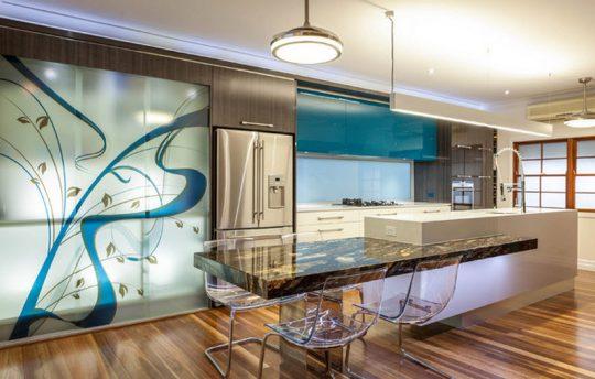 Moderna isla de cocina que esta empotrada en el mueble de color blanco, en conjunto con la decoración de cristales decorativo se ha conseguido un hermoso efecto