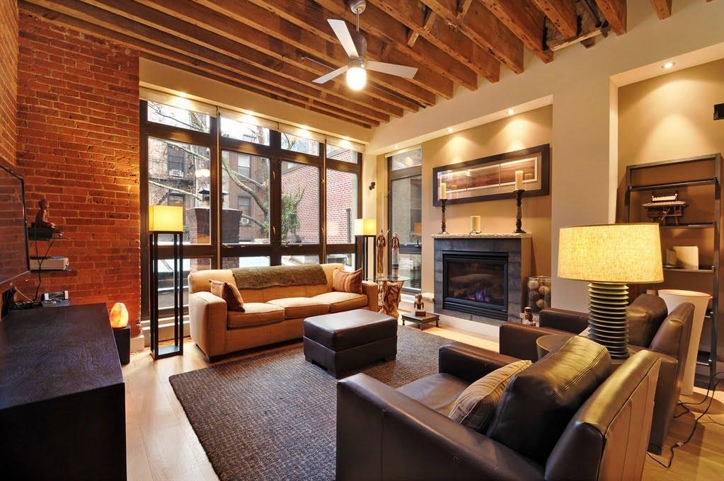 Una pared con ladrillo expuesto mas un techo de madera son el marco ideal de un acogedor diseño de apartamento, el elemento que tampoco puede faltar es la chimenea