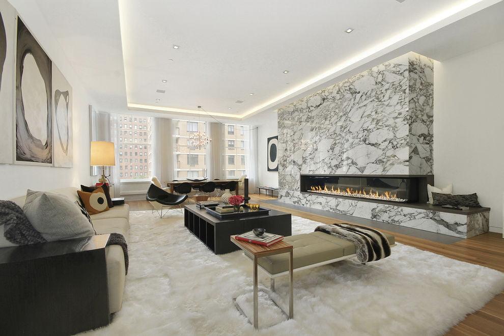 Exlusivo diseño de apartamento donde destaca una moderna chimenea y se combinaron los colores blanco y negro, un falso techo iluminado
