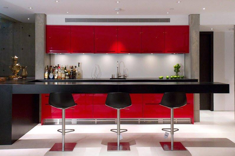 Muebles de color rojo y las encimeras e isla de cocina de color negro dan un interesante efecto para una casa de aspecto juvenil y moderno