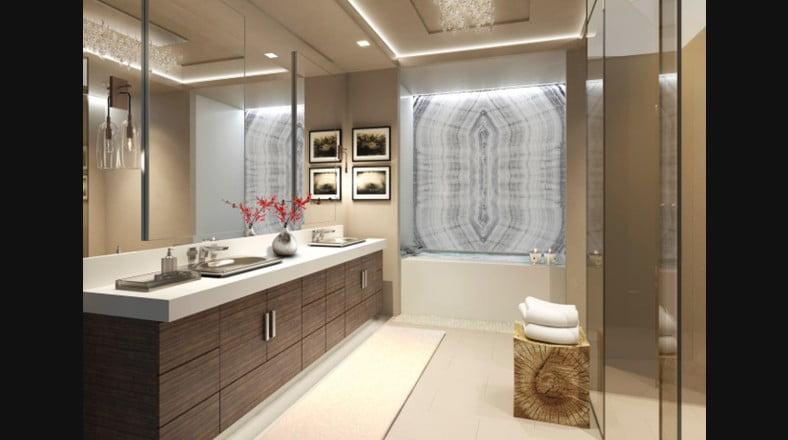 La decoración del cuarto de baño tiene grandes espejos en ambas paredes, el falso techo retroiluminado y un mueble de madera sostiene los lavabos