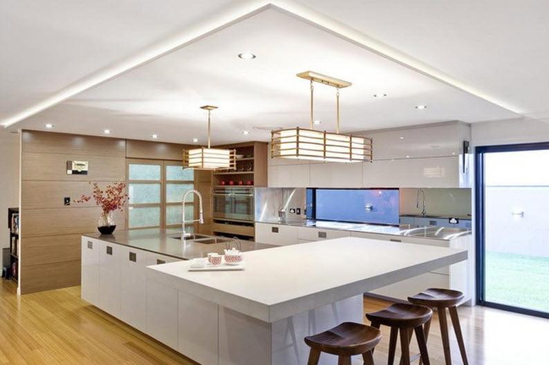 """Moderno diseño de cocina con encimera y muebles en color blanco y una """"hoja"""" que hace las veces de falso techo que delimita el espacio cuadrado de la cocina"""