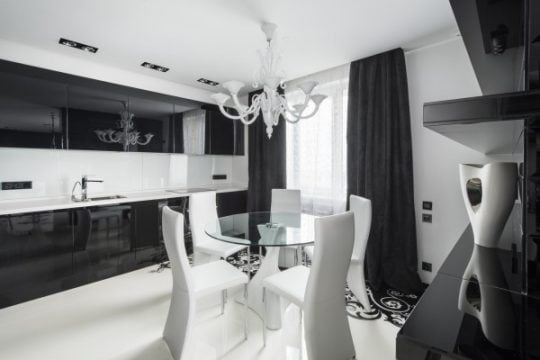 Diseño del comedor en color blanco a tono con la lámpara del mismo color, la cocina tiene muebles de color negro