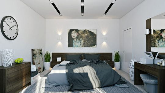 Un dormitorio que luce amplio gracias al color blanco aplicado a la paredes, normalmente en los cuartos se utiliza una pared que haga contraste de color en este caso son los muebles de madera color nogal los que consiguen este efecto decorativo (Pavel Vetrov)
