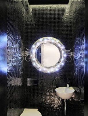 Luces Led alrededor del espejo del medio cuarto de baño le dan un aire futurista, los diseños de azulejos en color negro brillante complementan la decoración