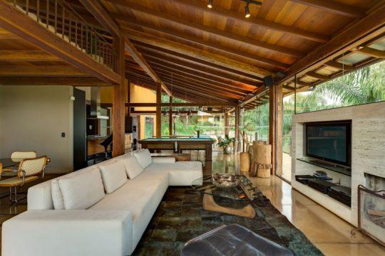 En el interior de la casa se luce la madera como elemento principal del diseño, se han colocado muebles blancos que hacen juego con un muro que hace las veces de mobiliario para televisor