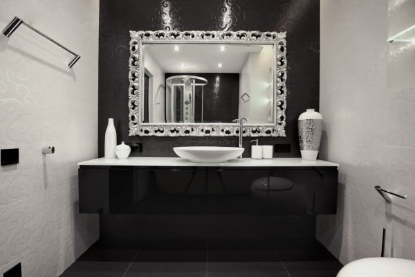 Un espejo con bordes plateados complementa el diseño de este moderno cuarto de baño, destacamos el uso de azulejos con acabados tipo textil
