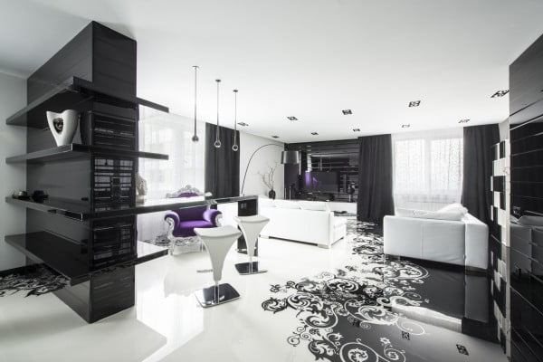 Esta vista muestra una panorámica de toda el área social del apartamento, como vemos el color blanco domina el ambiente y ha sido aplicado tanto a las paredes, como al techo y piso, un sillón de color lila es parte complementaria de la decoración de interiores