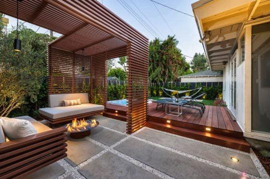 Tenemos un foto panorámica de toda la terraza con el modulo de listones de madera para definir el área principal, fíjate en las texturas del piso y la mesa al centro con fuego