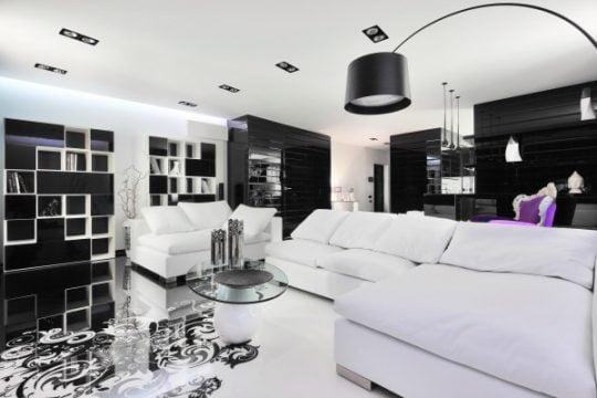 En el diseño de la sala del apartamento destaca el trabajo artístico en el piso, así como el tipo de iluminación, la estantería en color negro no opaca ni oscurecen el ambiente iluminado de la sala