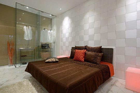 Vista del dormitorio donde se puede apreciar el closet transparente lo que permite hacer lucir las prendas de vestir y se convierten en parte de la decoración