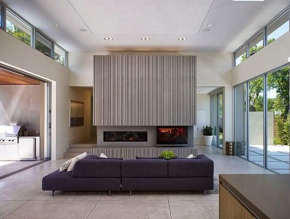 Parte del diseño de interiores y de manera funcional se ha colocado esta gran chimenea a uno de los costados del salón principal
