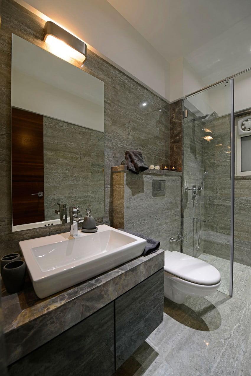 Diseño de cuarto de baño con mármol y sanitarios blancos