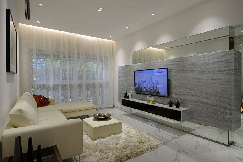 Diseño de la sala estar del moderno departamento, destacamos el muro de diseño marmoleado donde se coloca el televisor, tiene un espejo tanto en la parte superior e inferior lo que da la impresión de ser un muro flotante