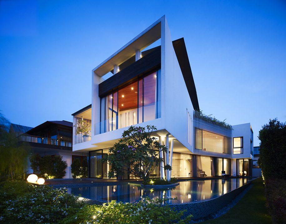 Vista de la casa por la noche, el espejo de agua le proporciona un toque de magia al diseño