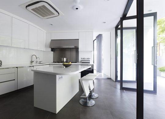 La cocina es completamente blanca y tiene un aire minimalista, destaca el diseño de los taburetes