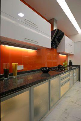Muebles de cocina inferiores transparentes con encimera de granito gris y muebles superiores de blanco brillante, al centro cerámica anaranjada
