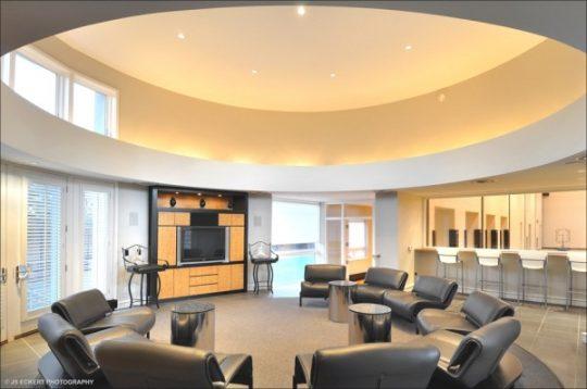 Un falso techo en forma de circulo es el elemento integrador para este salón de reuniones