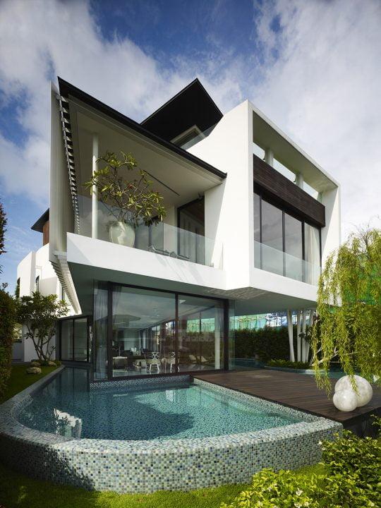 Diseño elegante de la fachada de la casa, tiene un ángulo de quiebre en el lado izquierdo, ademas de una estructura que se eleva sobre el techo lo que permite el control de los rayos solares y también como cerco de la azotea (Aemer Architects )