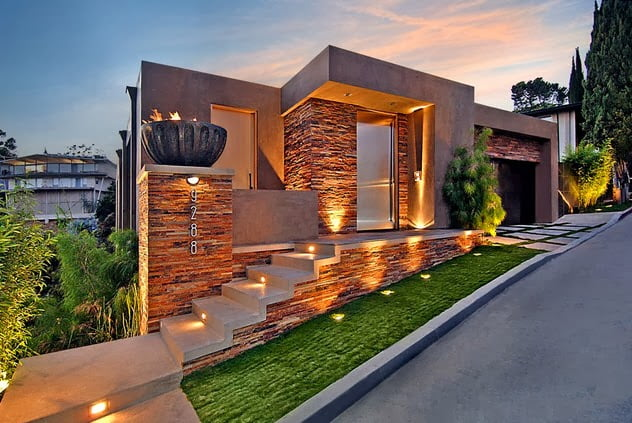 Fachada de la casa en piedra con iluminación prendida al anochecer (Arquitectos: Whipple Russel )