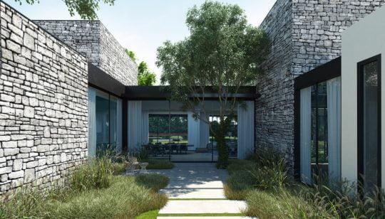 Camino que nos lleva a la zona social de la casa rodeado de paredes enchapadas en piedra