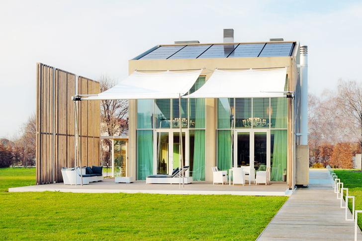 Dos grandes ventanas en la fachada de la casa permite el ingreso de luz natural a la vivienda, al costado una pared de varillas de madera permite filtrar los rayos solares y controlar los vientos (Construcción: Welldom)