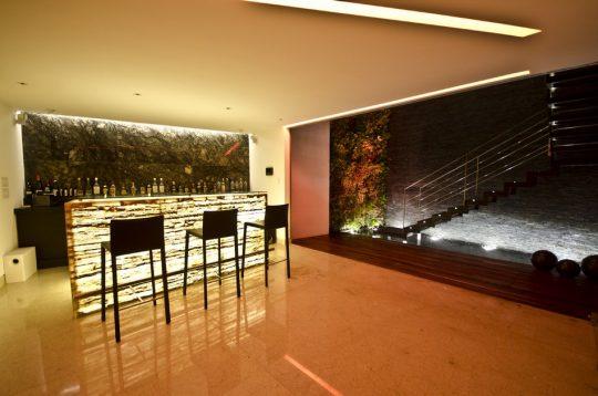 Diseño del moderno bar con una barra de ónix, el mismo material que hemos visto aplicado en la fachada
