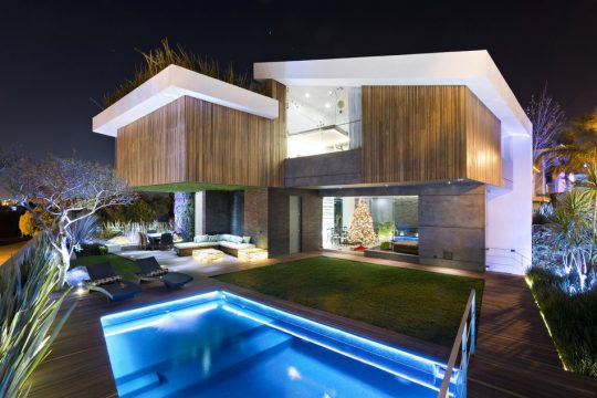 Fachada posterior con una perspectiva desde la piscina iluminada