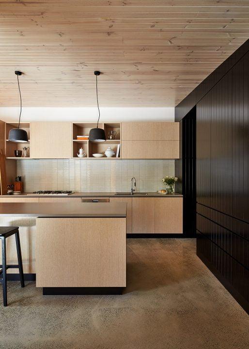 Vista frontal de la cocina con un muro de madera en color negro haciendo contraste
