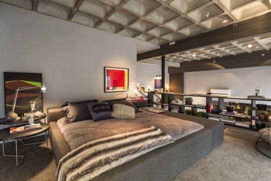 Diseño de dormitorio ubicado en el mezzanine del apartamento tipo loft, tonos grises en la decoración y el techo expuesto tipo industrial