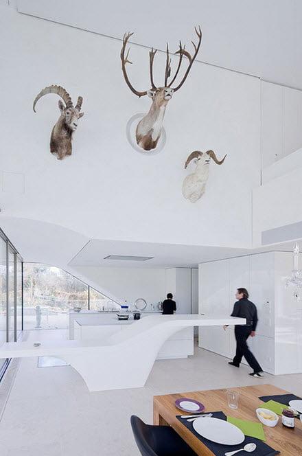 Los muebles de la cocina también tienen el carácter orgánico que hemos visto en todo el diseño del inmueble, las paredes y los muebles tienen el color blanco y sólo la mesa tiene un acabado de madera natural