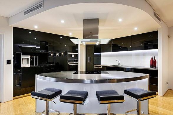 Cocina moderna con isla al centro, destaca por el brillo de los acabados tanto en reposteros como el cromado del metal