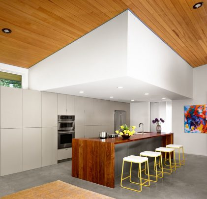 Diseño de la moderna cocina que se encuentra delimitada por un techo pintado en color blanco desde la cual recibe iluminación a través de spotlights