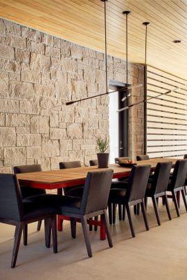 Diseño del comedor con paredes de piedra y techo de listones de madera de pino formando un conjunto armonioso y moderno