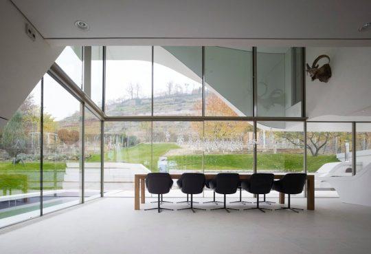 La sala comedor tiene un gran vista al exterior, podemos ver la ventana a doble altura que domina el diseño