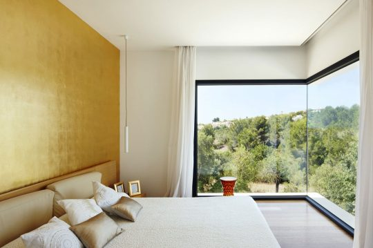 Diseño de dormitorio con una pared pintada de dorado