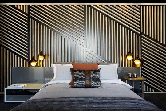 Se ha hecho un creativo trabajo con varillas de madera en la pared de la cabecera de la cama que se asemeja a un tejido