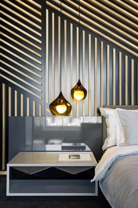 Mesa de noche e iluminación por lámparas colgantes del dormitorio que se ubica en el mezzanine del apartamento