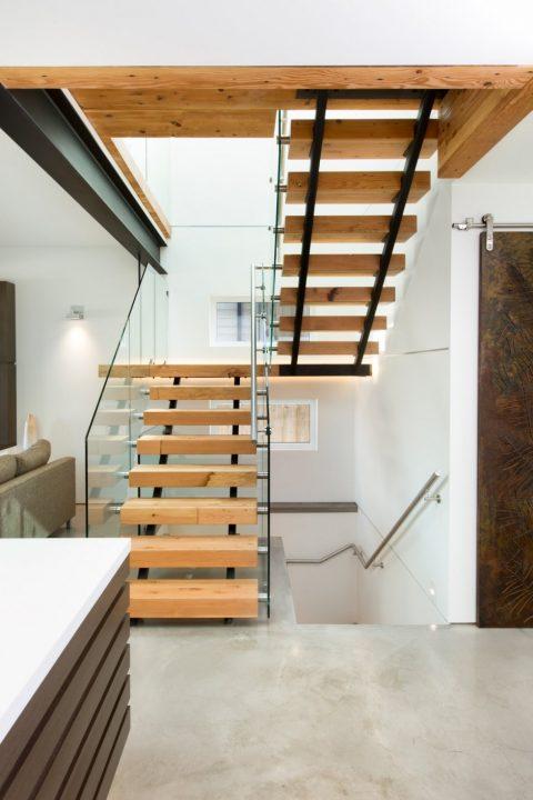 Diseño de escaleras con peldaños de madera y barandas de vidrio laminado