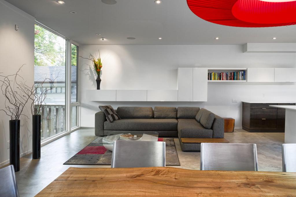Decoración de interiores de la sala es moderna, las paredes y techo tienen un color monocromatico gris claro, se ha agregado incluso muebles del mismo color que las paredes, en tanto los sofás son marrones , una gran lámpara de techo roja hace contraste con la decoración minimalista