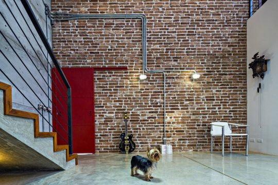 Diseño de la sala, podemos ver la paredes de fondo con el ladrillo e instalaciones eléctricas expuestas