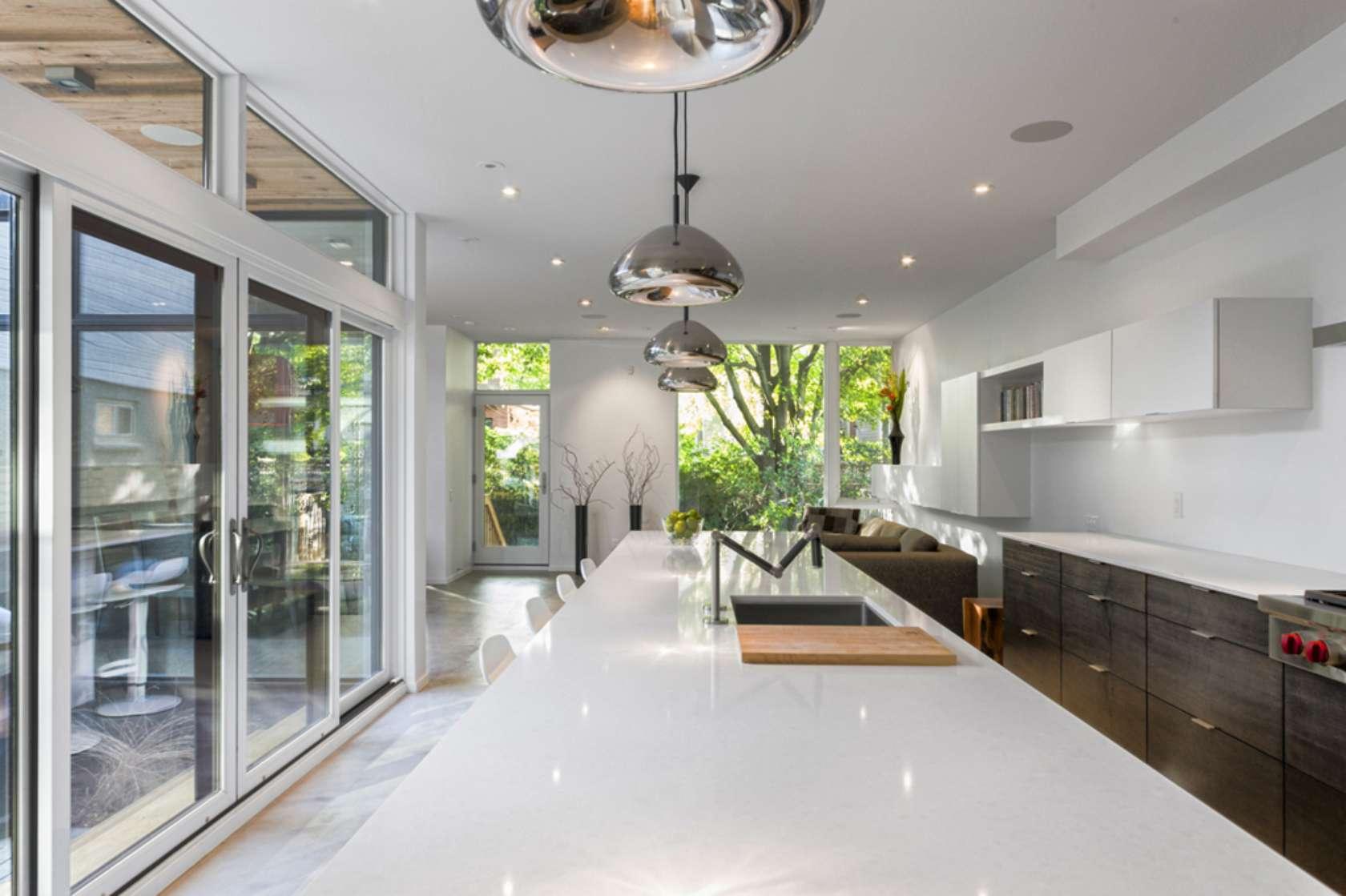 Diseño de isla de cocina lineal con grandes y modernas lámparas de techo cromadas