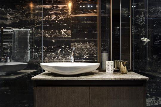 Se ha elegido azulejos oscuros en el cuarto de baño que contrastan con los sanitarios blancos