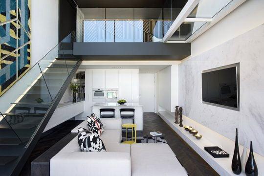 En esta vista podemos ver el minidepartamento en su totalidad, en el primer nivel la sala con la pequeña cocina, en el mezzanine se ubica el dormitorio que tiene como límite un vidrio templado