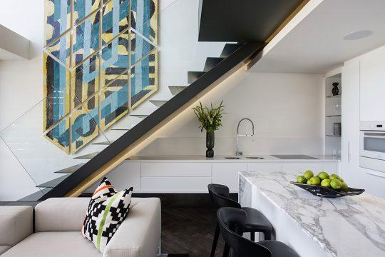 En esta vista podemos ver con mayor precisión el diseño de la cocina con su pequeña isla comedor, la escalera de peldaños de metal es un elemento fuerte de decoración dentro del departamento