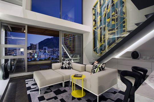 Diseño de interiores de la sala del minidepartamento, a pesar del pequeño espacio disponible se coloco un juego de muebles modular y debajo de la escalera -que se encuentra iluminada por uno de sus lados- se diseño la cocina (diseño: SAOTA)