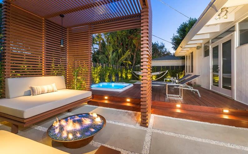 Diseño de hermosa terraza, en el primer plano podemos ver un mueble en color blanco protegido por una cubierta virtual de varillas de madera, al centro un jacuzzi y al final el diseño de una hamaca (Arquitecto Kurt Krueger)