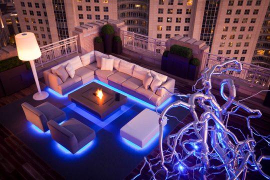 La luz es uno de los principales elementos de la decoración de interiores, si quieres conseguir un diseño de terraza moderno debes saberlo emplear, en la foto podemos ver que se han colocado punto de luz debajo del juego de muebles que cambian según el estado de animo que se quiere conseguir (Harold Leidner)