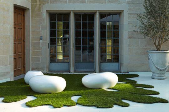 Grass sintético recortado en formas ondulantes, encima de ella se han colocado muebles cerámicos (Grace Design Associates)